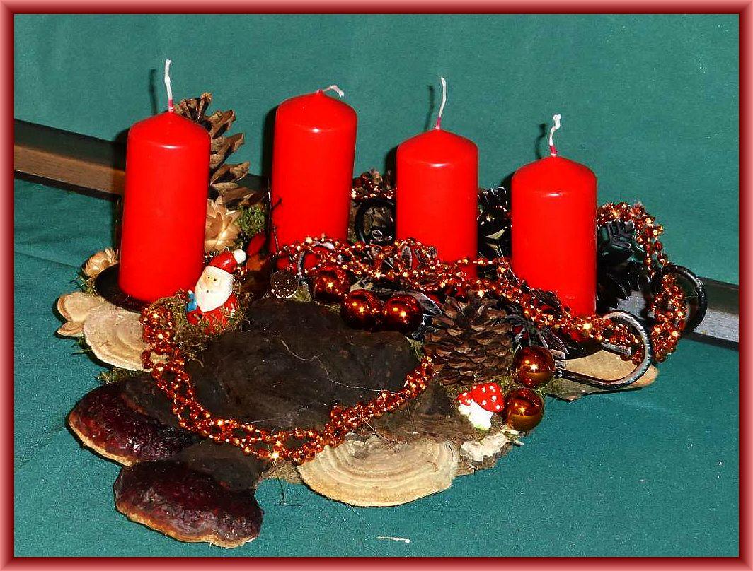 29. Dreieckiges 4er Gesteck auf Baumscheibe mit Schlitten, Rotrandigen Baumschwämmen, Striegeligen Trameten, Zapfen, altgoldener Weihnachtsdekoration und roten Stumpenkerzen zu 12.50 €.