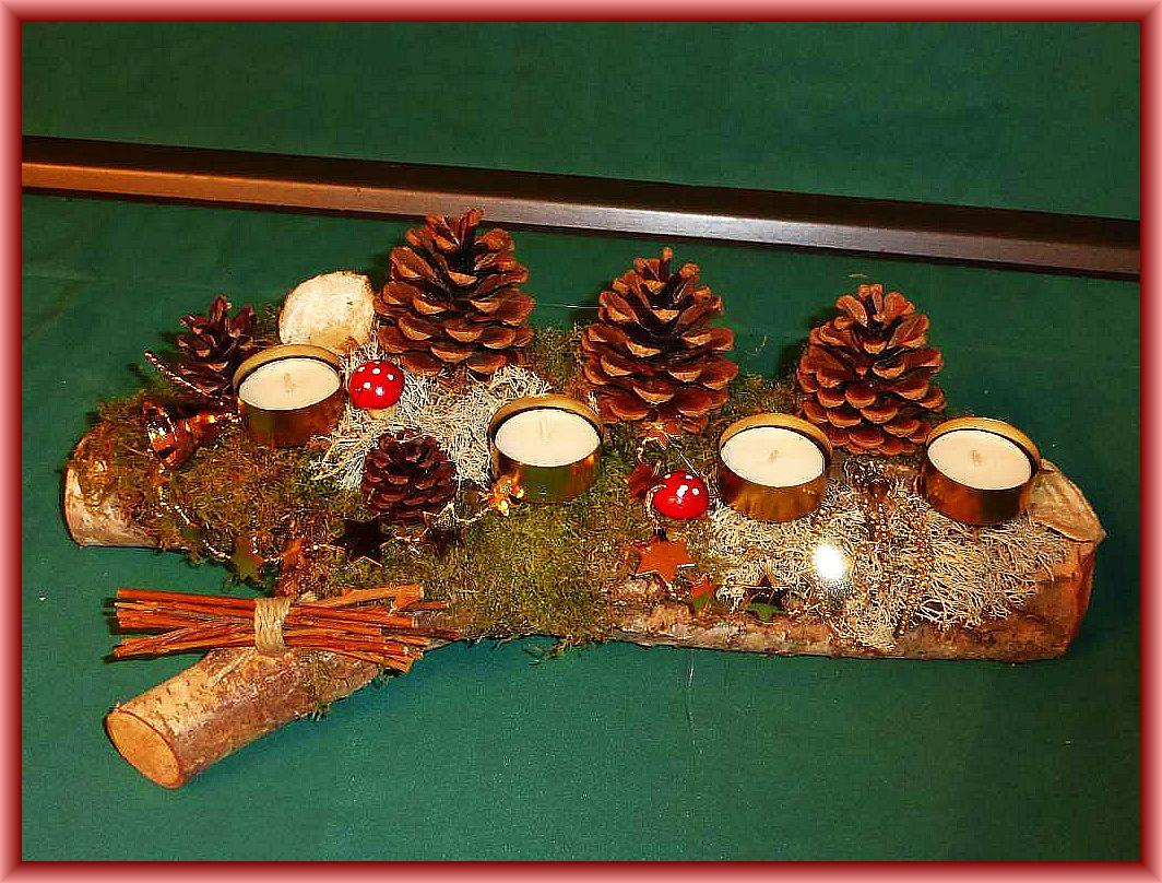 31. Etwa 40 cm langes, bis 15 cm tiefes er Gesteck mit Teelichtern auf Birkenstamm mit Moos, Reintierflechte, Kiefernzapfen und Weihnachtsdekoration zu 8.00 €.