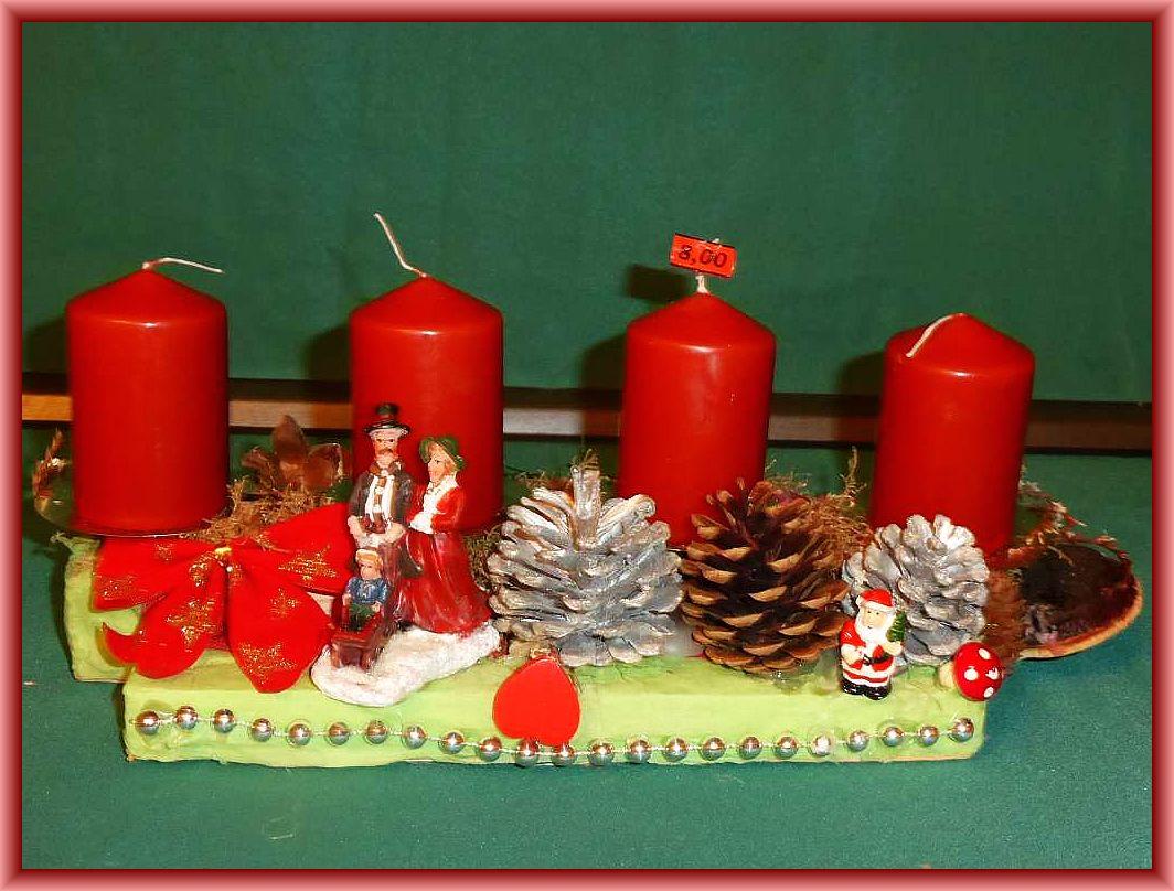 31. Längliches 4er Gesteck auf Holzleisten in hellrünen Servietten eingeschlagen, weinbrauenen Stumpebkerzen, Moos, silbernen Kiefernzapfen, Familie und Weihnachtsdeko zu 8.00 €.