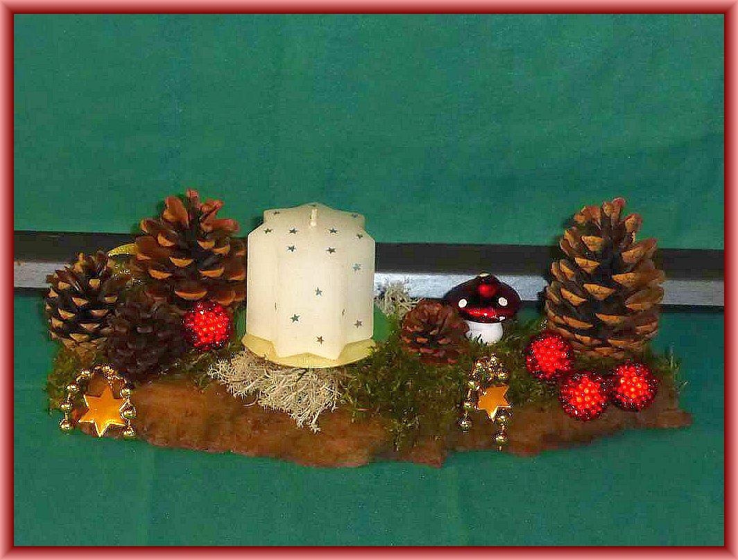 34. Etwa 25 cm langes, bis 10 cm tiefes 1er Gesteck mit weißer Sternkerze auf stabiler Baumrinde, Moos, Rentierflechte, Kiefernzapfen und Weihnachtsdekoration für 8.00 €.