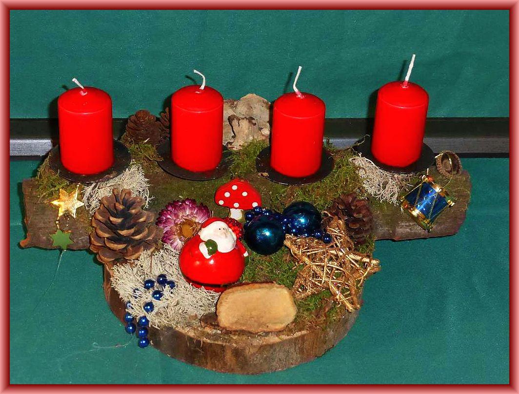 35. Rundliches Gesteck auf Baumscheibe und stabiler, ausgreifender Baumrinde mir 4 roten Stumpenkerzen, Moos, Rentierflechte, Rotrandigem Baumschwamm, Zapfen und Weihnachtsdekoration für 10.00 €.