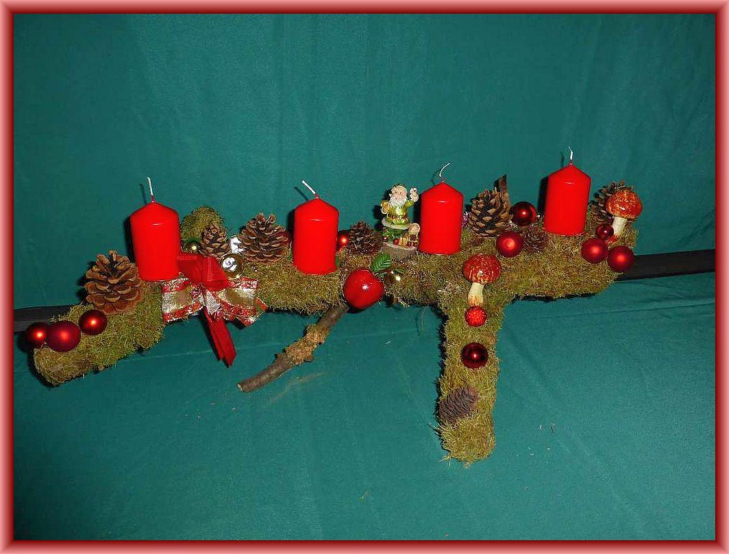 38. Großes, ausladendes 4er Gesteck auf Astgabel, etwa 80 cm lang und bis 40 cm tief mit Moos, Kiefernzapfen, Eichenwirrling, künstlichen Pilzen und Weihnachtsdekoration für 15.00 €.