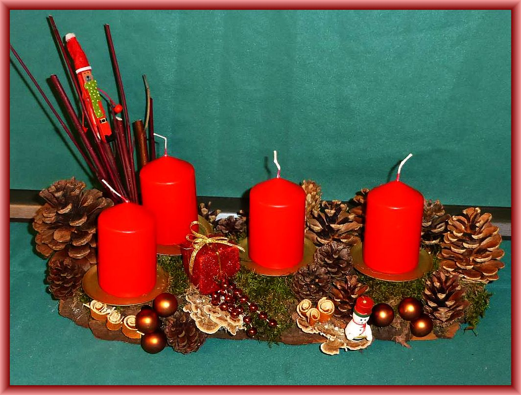 41. Knapp 40 cm langes und 15 cm tiefes 4er Gesteck auf stabiler Baumrinde, mit roten Stumpenkerzen, Moos, vielen Kiefernzapfen, Hartriegel und Weihnachtsdeko zu 12.50 €.
