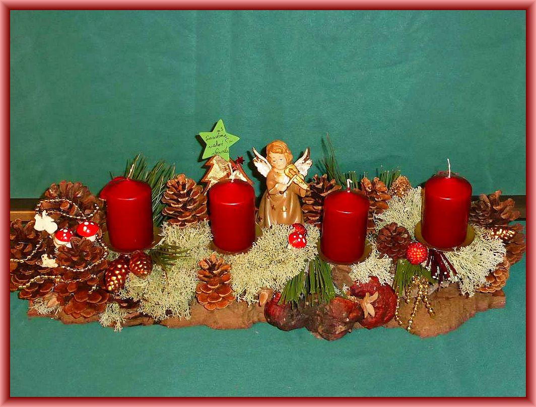 42. Etwa 50 cm langes, 20 cm tiefes 4er Gesteck mit burgundfarbenen Stumpenkerzen auf satbiler Baumrinde  mit viel Rentierflechte, Kiefern- und Weihnachtsdekoration und Engel für 25.00 €.