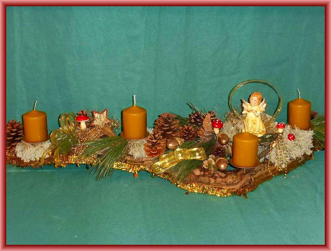 44. Etwa 1 m langes, bis 25 cm tiefes 4er Gesteck auf Baumrinde Stumpenkerze in Tundra, Kieferndeko, Rentierflechte, Engel und filigraner, in gold gehaltener Weihnachtsdekoration zu 30.00 €.