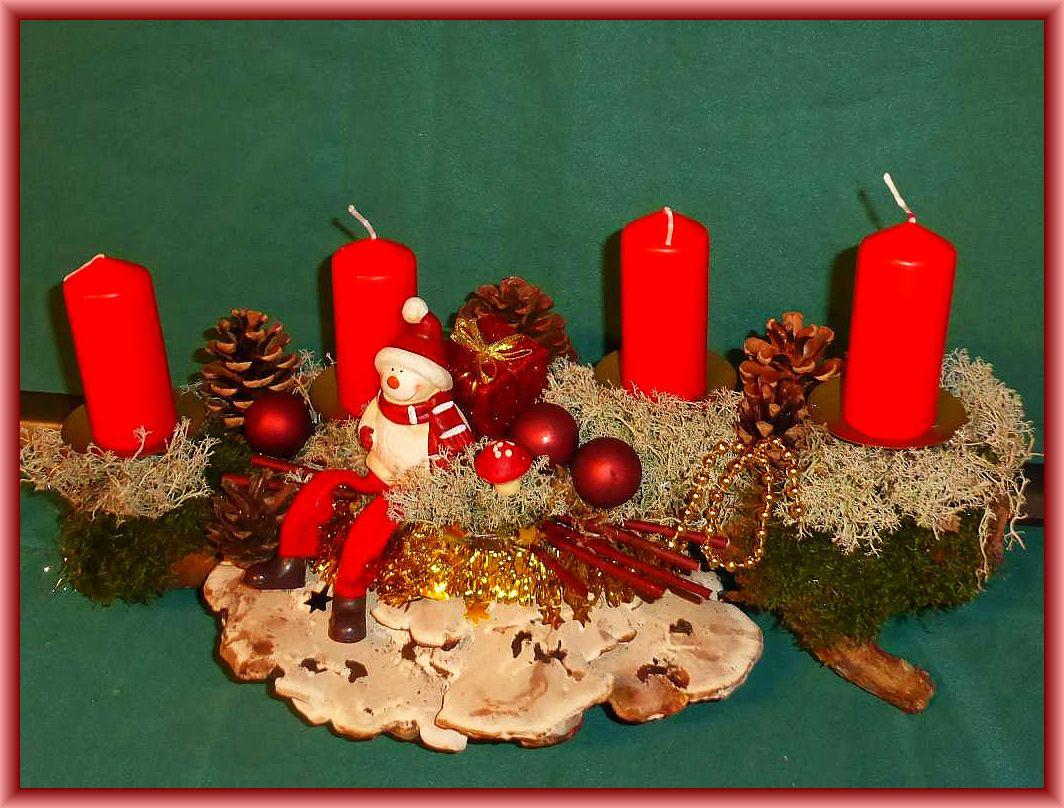 47. Etwa 40 cm langes, bis 25 cm tiefes 4er Gesteck mit roten Stumpenkerzen, auf Astgabel mit Flachem Lackporling, Moos, Rentierflechte, Kiefernzapfen, Weihnachtsfigur und roter Deko zu 20.00 €.