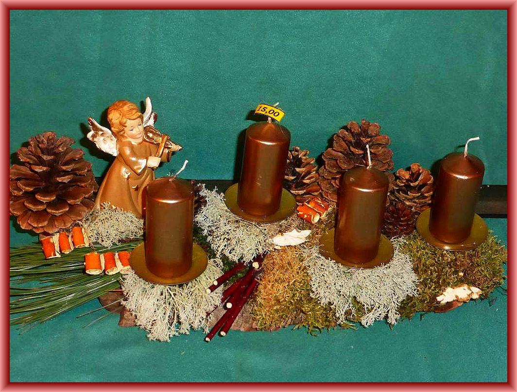 48. Gut 40 cm langes, bis 15 cm tiefes 4er Gesteck mit bronzefarbenen Glanzkerzen auf stabiler Baumrinde mit Moos, Rentierflechte, Kieferndekoration, gerollten Orangenschalen mit Engel zu 15.00 €.
