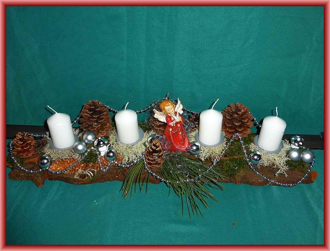 Etwa 70 cm langes, 15 cm tiefes 4er Gesteck mit weißen Stumpenkerzen, Moos, Rentierflechte, Schmetterlingstramete, Kiefernzapfen, Engel und in silber gehaltener Weihnachtsdekoration zu 25.00 €.