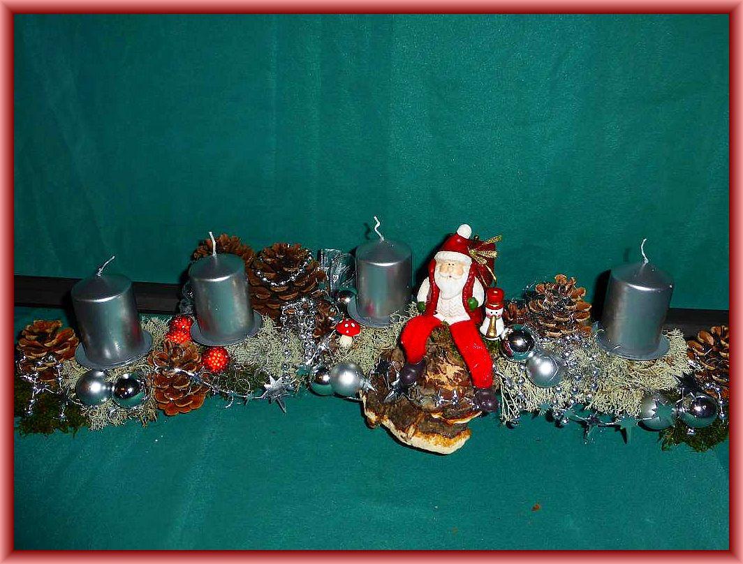 Eisiges Hochwinterliches Adventsgesteck , etwa 60 cm lang, 20 cm tief in silber gehaltener Weihnachtsdekoration und silbernen Glanzkerzen auf Astgabel mit Rentierflechte, auf Rotrandigem Baumschwamm sitzendem Weihnachtsmann zu 20.00 €.