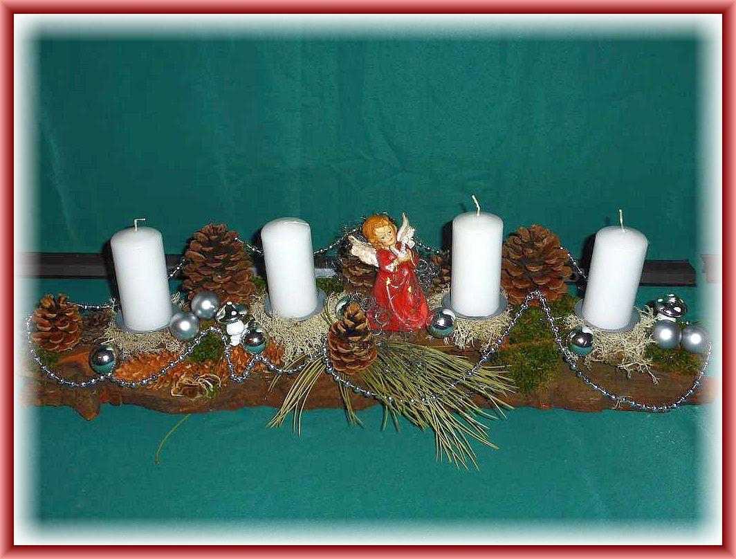 Etwa 70 cm langes und 15 cm tiefes 4er Gesteck mit weißen Stumpenkerzen, Moos, Rentierflechte, Schmetterlingstramete, Kiefernzapfen, Engel und in silber gehaltener Weihnachtsdekoration zu 20.00 €.