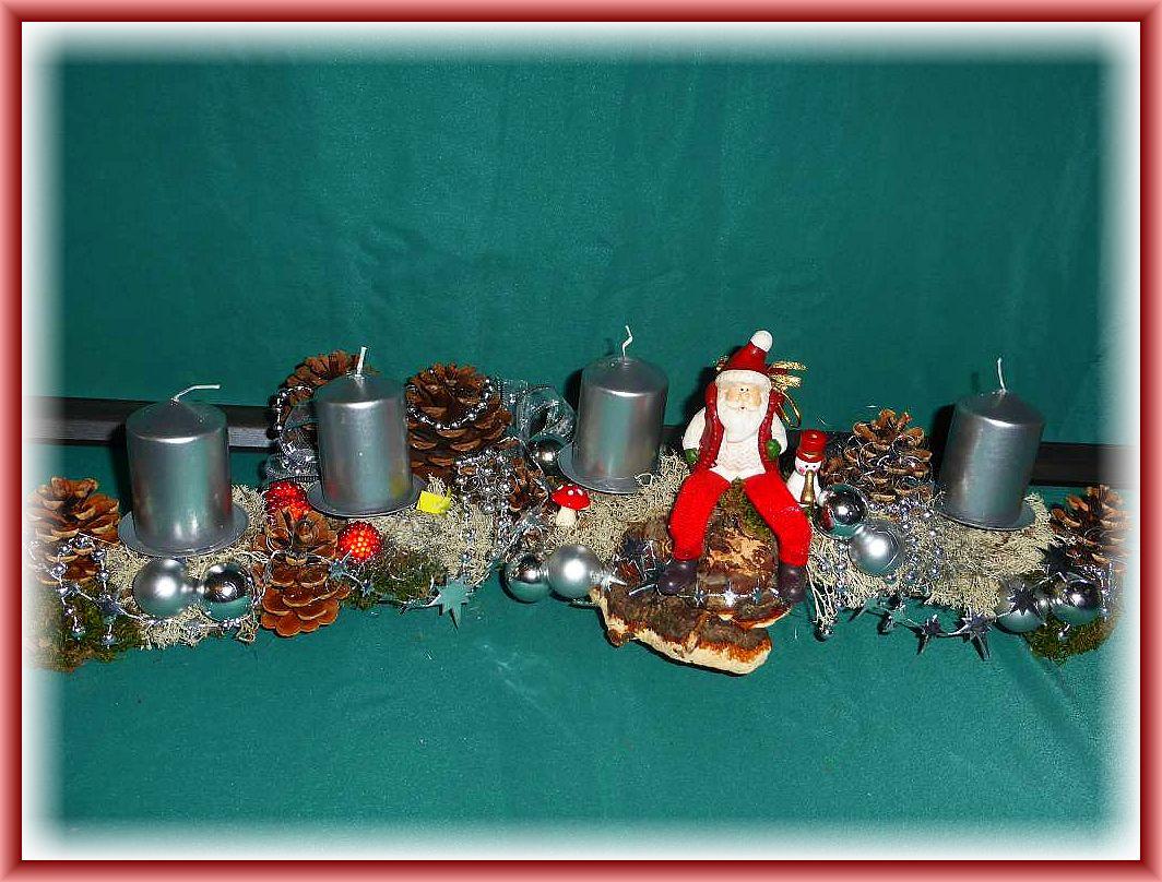 9. Eisiges Adventsgesteck, etwa 60 cm lang, 20 cm tief in silber gehaltener Weihnachtsdekoration und 4 silbernen Stumpenkerzen auf Astgabel mit Rentierflechte, Weihnachtsmann auf Rotrandigem Baumschwamm sitzend für 20.00 €.