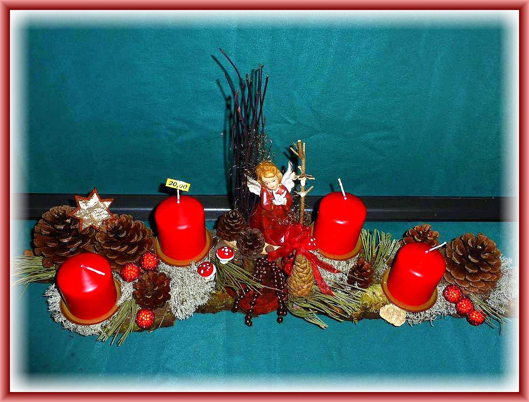 12. Etwa 60 cm langes, 15 cm tiefes 4er Gesteck mit roten Stumpenkerzen auf stabiler Baumrinde, Rentierflechte, Schmetterlingstramete, Zapfen, Kieferndeko, mittigem Engel und weiterer Weihnachtsdekoration zu 20.00 €.