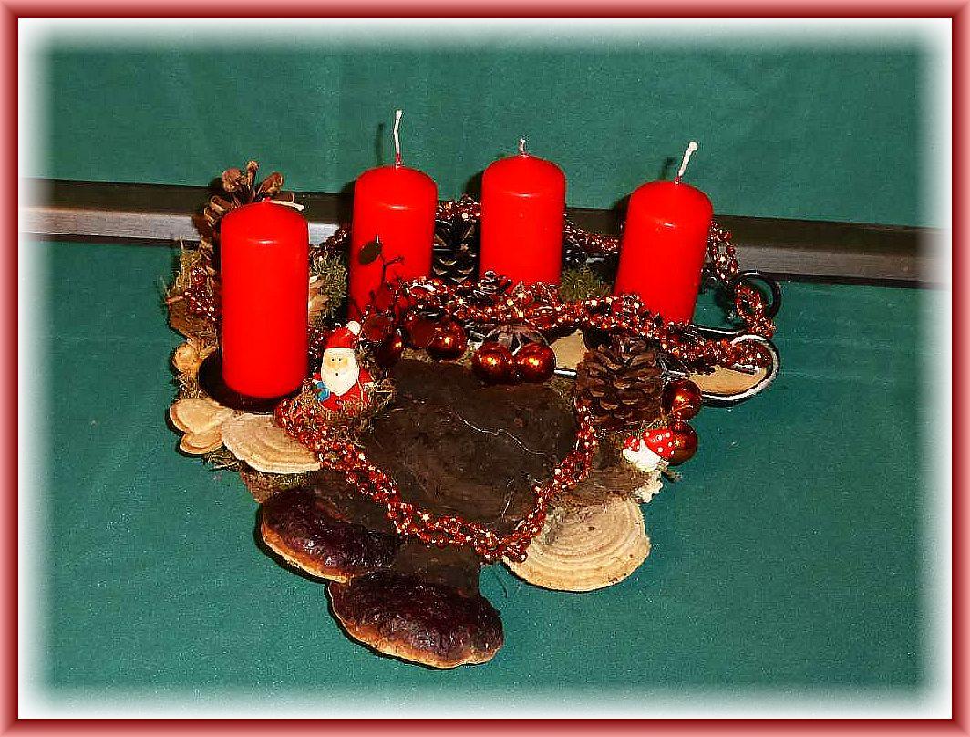 19. Dreieckiges 4er Gesteck mit etwa 30 cm im Durchmesser auf Baumscheibe mit dunklem Schlitten, Rotrandigem Baumschwamm, Striegeligen Trameten, Zapfen, altgoldener Weihnachtsdekoration und roten Stumpenkerzen zu 12.50 €.