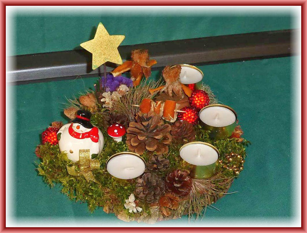 Rundes 4er Gesteck mit Teelichtern auf Baumscheibe, etwa 20 cm im Durchmesser mit Moos, dickem Schneemann und reichlich weiterer Dekoration mit Stern zu 8.00 € - Verkauft.