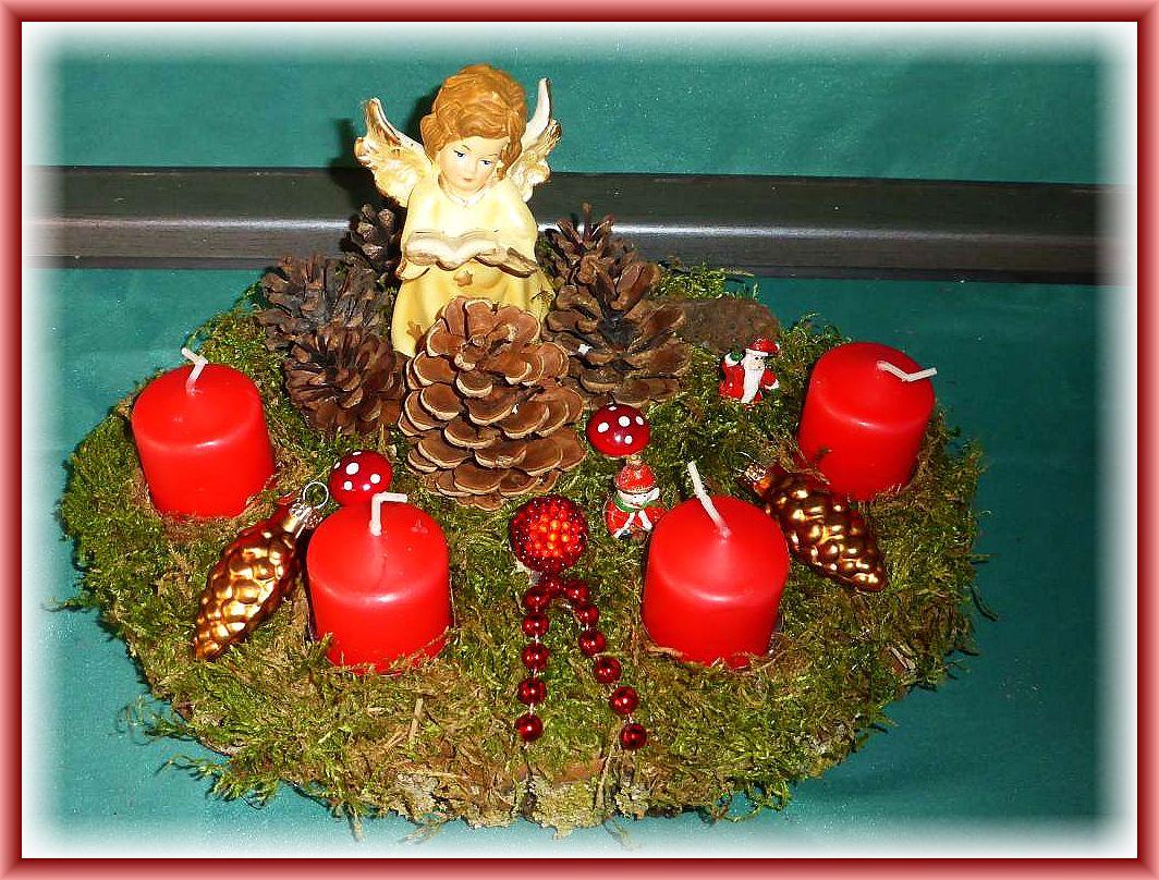 Ovales 4er Gesteck auf Baumscheibe mit Moos, Kiefernzapfen, Eingel, Weihnachtsdekoration und roten Stumpenkerzen, 30 cm im Durchmesser für 10.00 €.