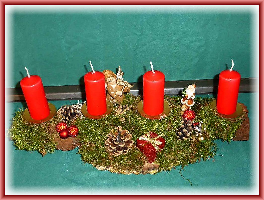 Etwa 35 cm langes, bis 15 cm tiefes 4er Gesteck auf Holzscheibe und stabiler Baumrinde, Moos, Engel und Weihnachtsamann, Kiefernzapfen und noch etwas Dekoration zu 12.50 €.
