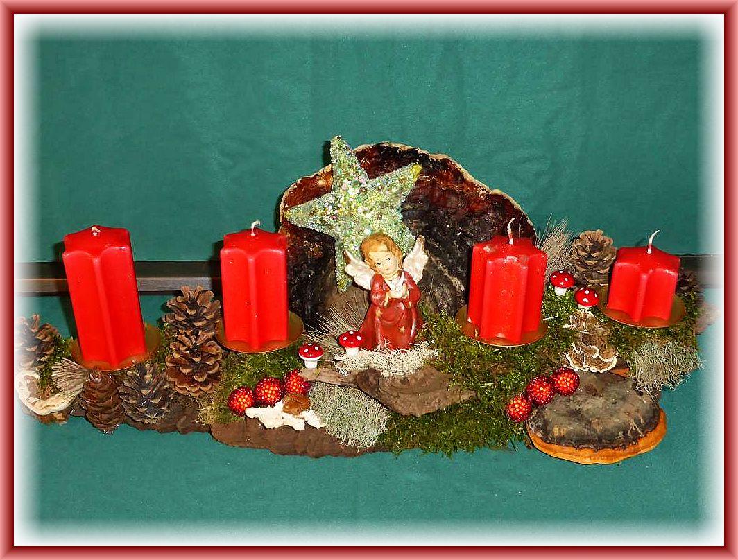 Längliches 4er Gesteck auf stabiler Baumrinde, etwa 50 cm länge, 20 cm tief, mit Rotrandigen Baumschwämmen, Schmetterlingstrameten, Wurzelschwamm, Kiefernzapfen, Engel und Glitzerstern und weiterer Weihnachtsdekoration zu 25.00 €.