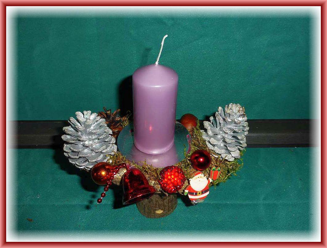 Hochbeiniges 1er Gesteck auf Holz mit helllila Stumpenkerze, Moos, silbernen Kiefernzapfen und Weihnachtsdekoration zu 5.00 €.