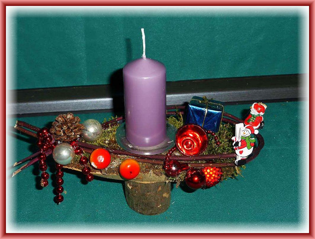Kleines, hochbeiniges Gesteck auf Rundholz mit hellila Stumpenkerze mit Moos, Hartriegel und Weihnachtsdekoration zu 5.00 €.