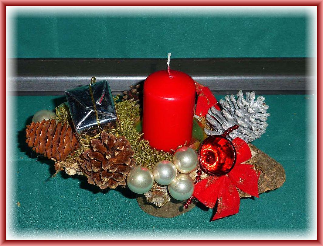 30. Kleines, hochbeiniges 1er Gesteck auf Rundholz mit roter Stumpenkerze, Moos, Zapfen und Weihnachtsdekoration zu 6.00 €.