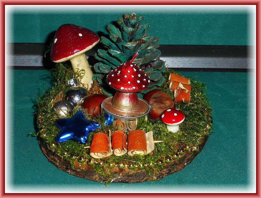 Rundes 1er Gesteck auf Holzscheibe, etwa 15 cm im Durchmesser mit Moos,grünem Kieferzapfen als Tannenbaum mit großem Pilz, weiterer natürlicher und künstlicher Dekoration und Fliegenpilz - Teelicht für 8.00 €.