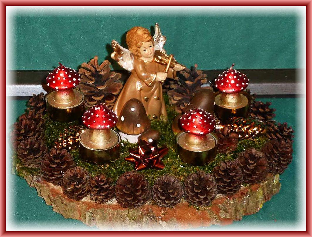 Rundes 4er Gesteck auf Baumscheibe umrandet mit Kiefernzapfen, ca. 25 cm im Durchmesser mit Moos, Engel, Deko - Pilzen und Fliegenpilz - Teelichtern zu 12.50 €.