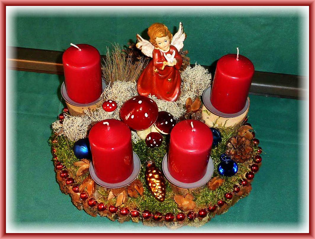 Rundes und kompaktes 4er Gesteck auf Baumscheibe mit roten Stumpenkerzen, etwa 30 cm im Durchmesser, mit Moos, Rentierflechte, Kiefernzapfen, Buchenfruchtschalen, Engel, Pilzgruppe und Perlenkette als Umrandung zu 20.00 €.