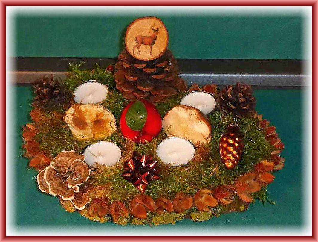 41. Rundes 4er Gesteck mit Teelichtern auf Baumscheibe mit Buchenfruchtschalen - Umrandung, Moos, Rotrandigen Baumschwämmen, Kiefernzapfen, Schmetterlingstrameten und weiterer Dekoration, etwa 25 cm im Durchmesser für 10.00 €.