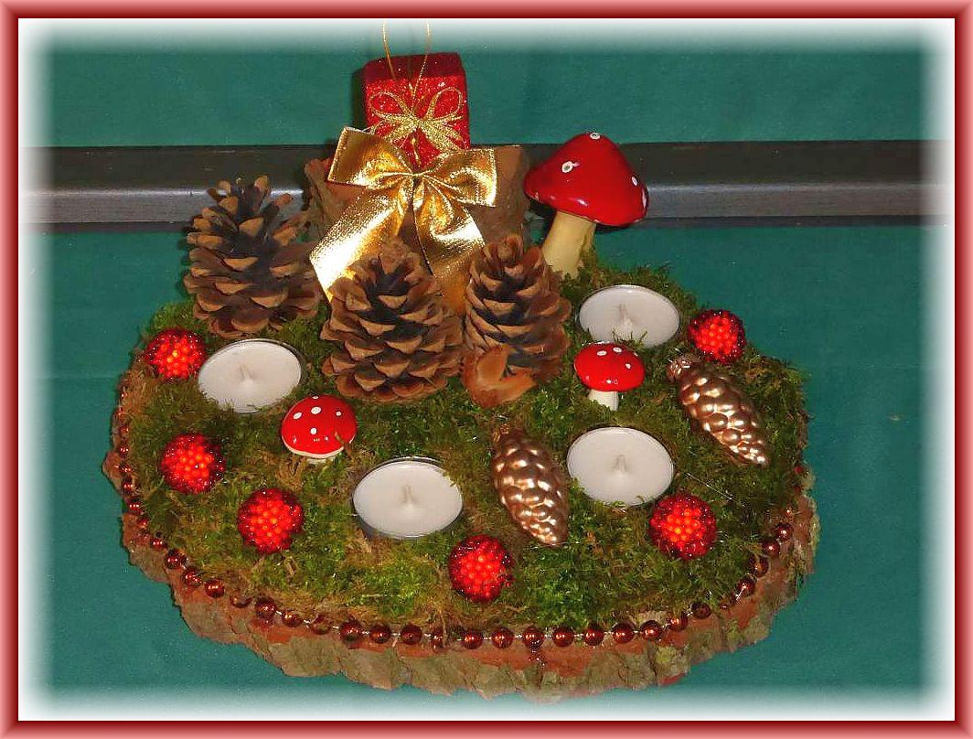 45. Rundes 4er Gesteck, mit Teelichtern auf Holzscheibe, Moos, Kiefernzapfen, Fliegenpilze und weiterer Dekoration, Perlenumrandung, etwa 25 cm im Durchmesser zu 12.50 €.
