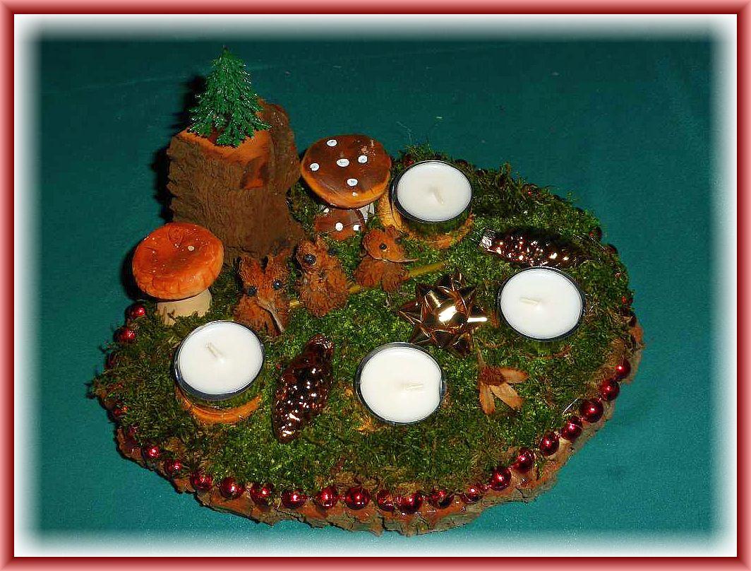 46. Rundliches 4er Gesteck auf Holzscheibe mit Teelichtern, Moos, Tannenbaum auf Felsen (Holz), Buchenvöglein, Pilzen und weiterer Dekoration, etwa 20 cm im Durchmesser für 10.00 €.
