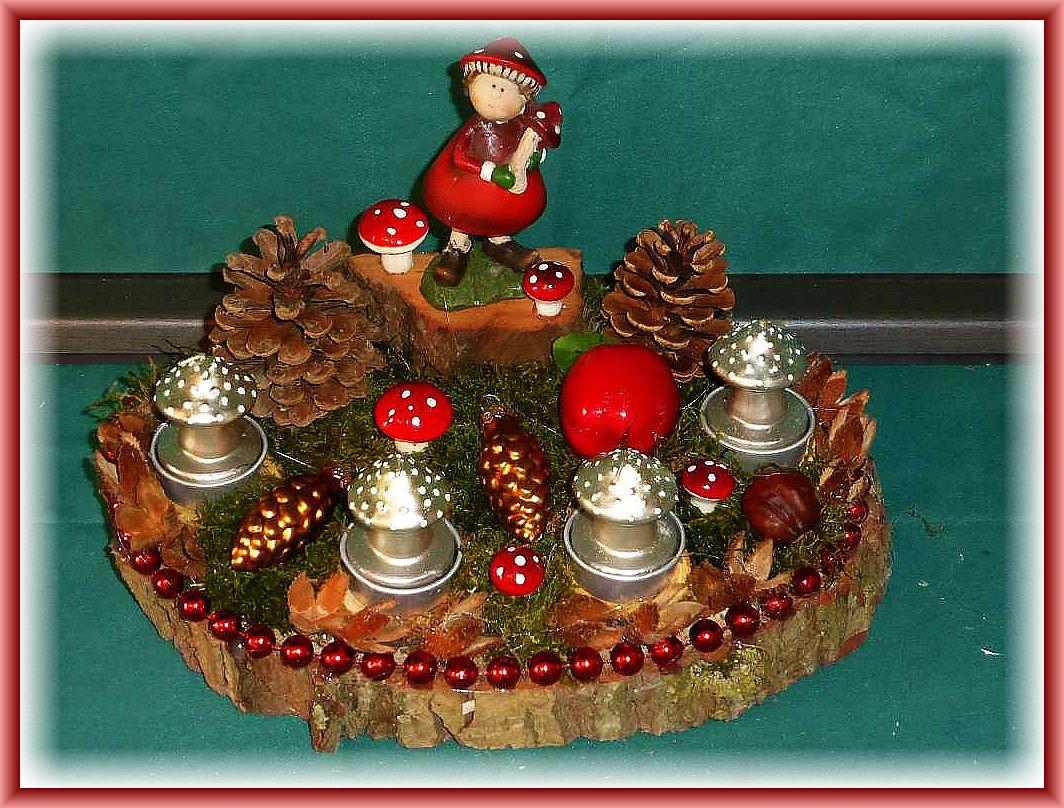 47. Rundlich ovales 4er Gesteck auf Holzscheibe mit Moos, Buchenfruchtschalen, Kiefernzapfen, Fliegenpilzfigur auf Holzsockel und weiterer Dekorarion, roter Perlenumrandung, etwa 30 cm im Durchmesser und Pilzkerzen zu 12.50 €.