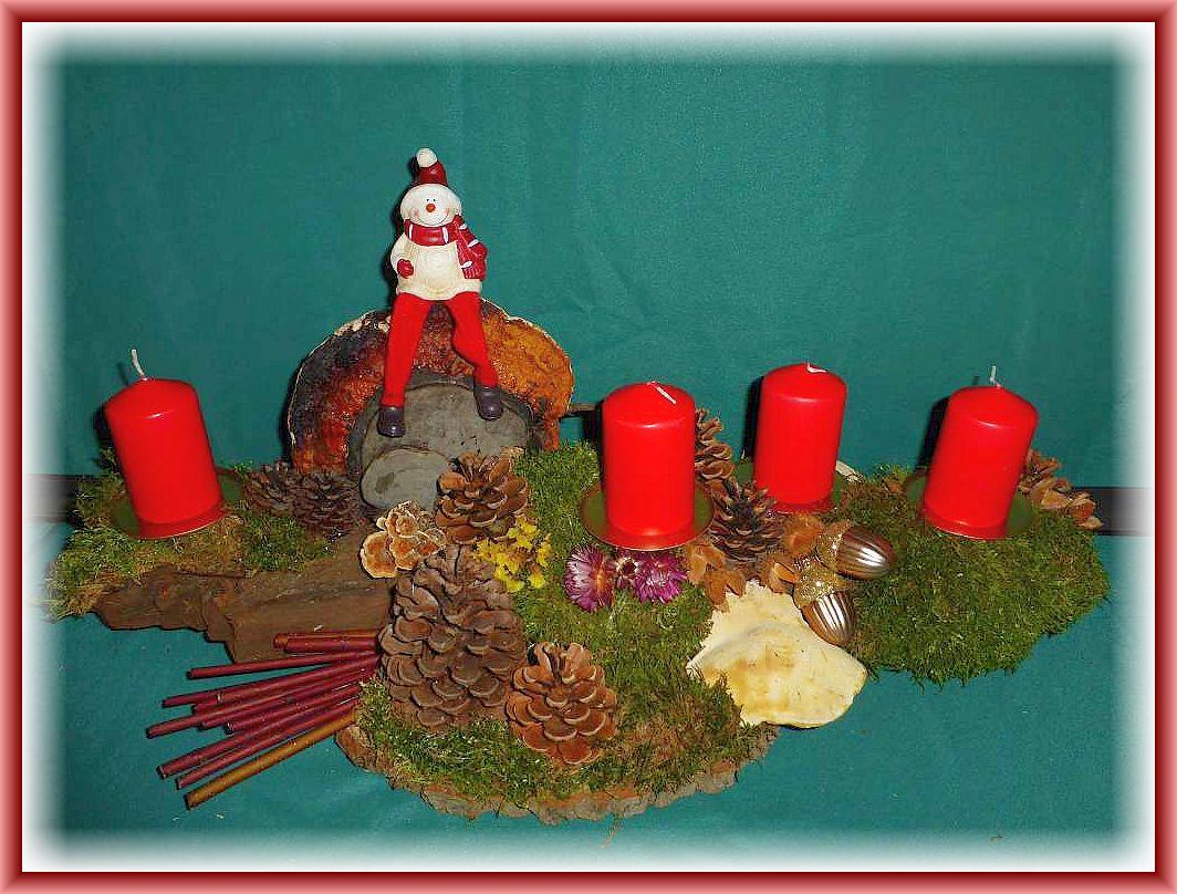 54. Großes 4er Gesteck auf Baumscheibe und stabiler Baumrinde, etwa 60 cm lang, bis 20 cm tief, mit Rotrandigen Baumschwämmen, Buckeltramete, Schmetterlingstramete, Moos, Kiefernzapfen, Strohblumen, Buchenfruchtschalen, Hartriegel und Weihnachtsfigur zu 20.00 €.
