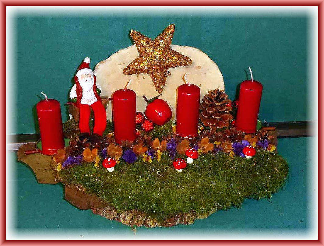 55. Großes, kompaktes 4er Gesteck mit dunkelroten Stumpenkerzen, etwa 50 cm lang, 20 cm tief und 25 cm hoch auf Baumscheibe, stabiler Baumrinde, Rotrandigem Baumschwamm, viel Moos, Kiefernzapfen, Buchenfruchtschalen, Fliegenpilzen, Weihnachtsmann und Goldstern zu 25.00 €.
